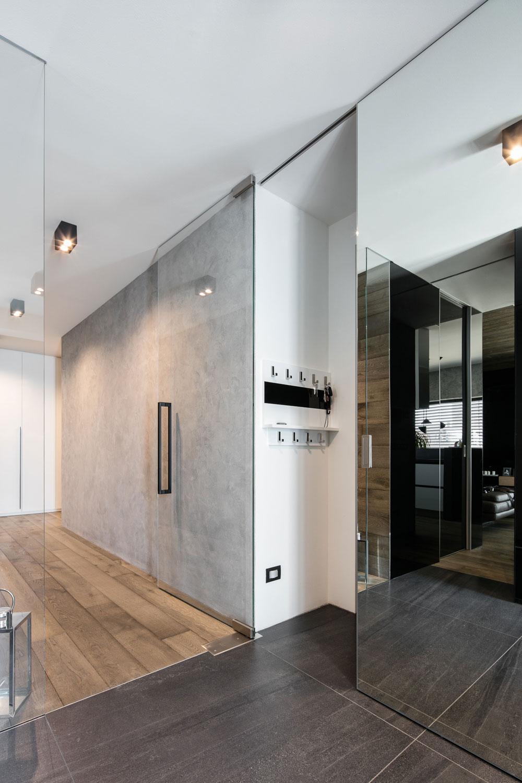 Dominantním prvkem vstupního prostoru rodinného domu v Olomouci jsou velkoformátové dveře MASTER DOOR se zrcadlovým povrchem v posuvném systému PREMIUM který je kotvený ve stropě.