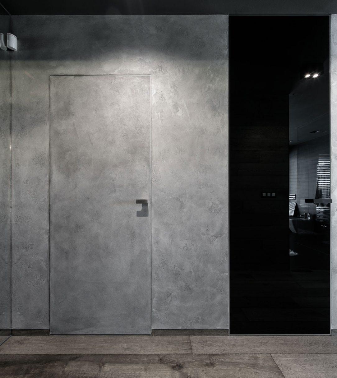 Penetrovaná MDF deska na dveřích MASTER DOOR nese na svém povrchu betonovou stěrku ze sousedící stěny.