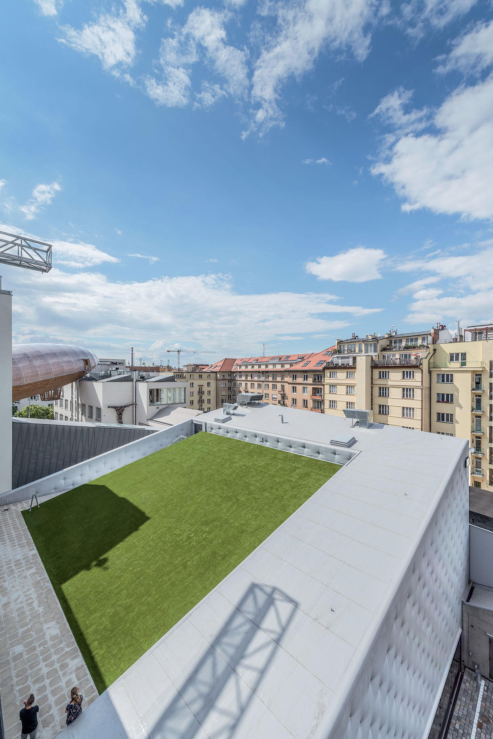 Zatravněná šikmá střecha slouží jako relaxační zóna ze které je možné sledovat akrobatická vystoupení tanečníků zavěšených na lanech