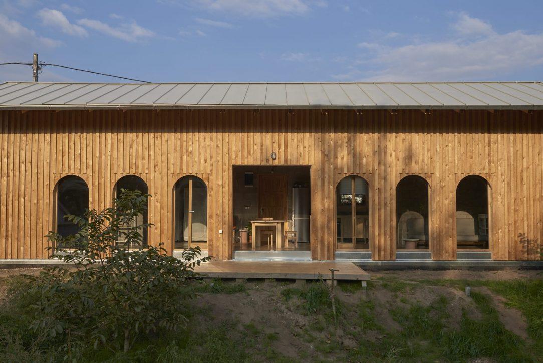 Absolutním opakem je druhá tvář tohoto domu tu tvoří šest velkých oken sahajících po zem