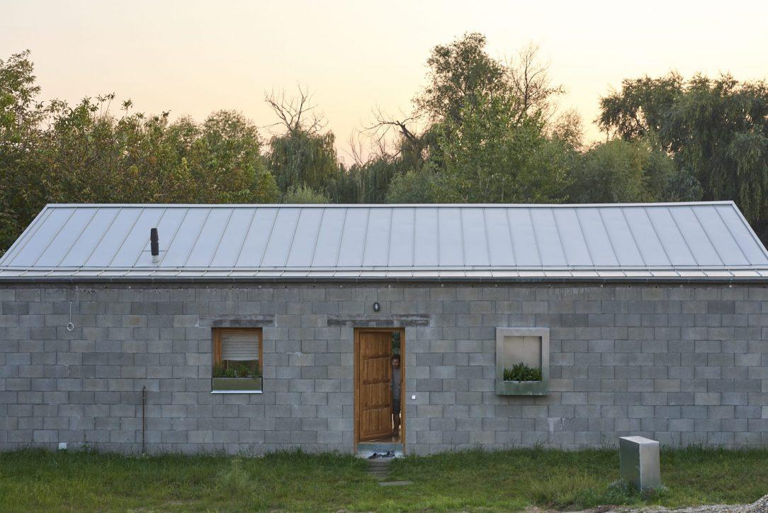 Dům s nízkou sedlovou střechou leží na dlouhém užším pozemku