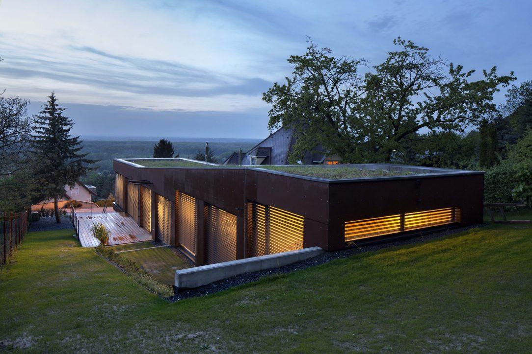 Parcela stoupá k lesu a stavba je tak vidět z nadhledu avšak bezúdržbová vegetační střecha jej maskuje a nechává splynout s okolní zelení.