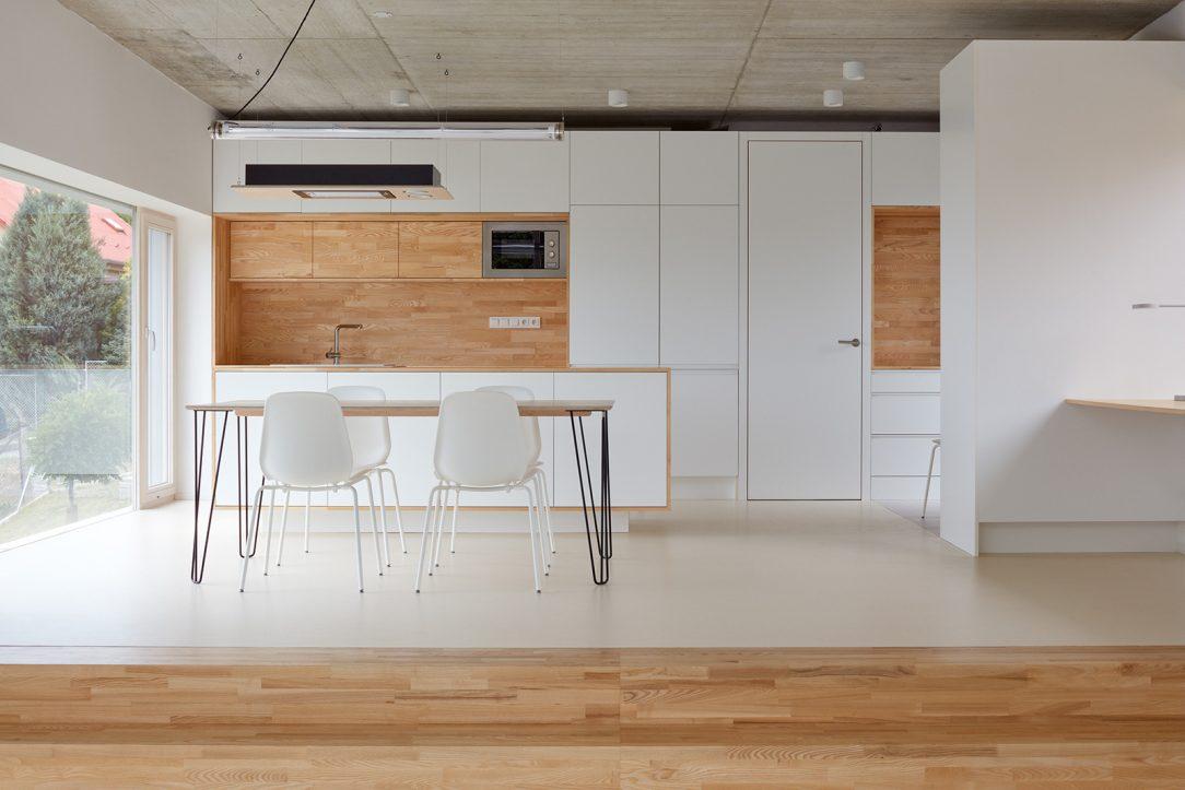 Světlé odstíny a dřevo prostupují z fasády i do interiéru kterému dominuje jemná kombinace bílé a dřevěných prvků.