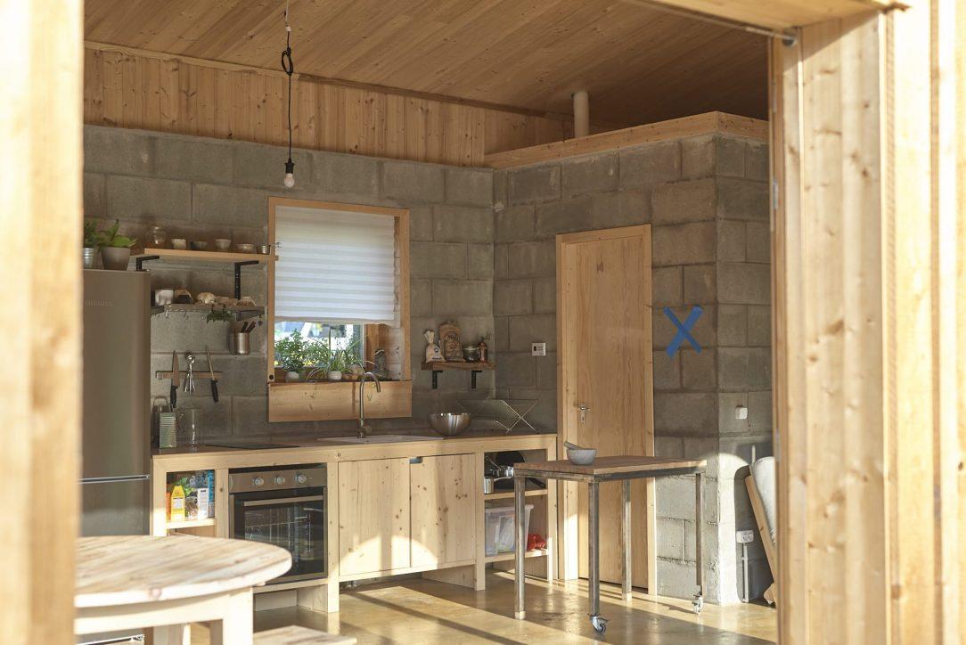 Vyzývavý kontrast k němu tvoří šedé zdivo v hlavním obytném prostoru za kuchyňskou linkou.