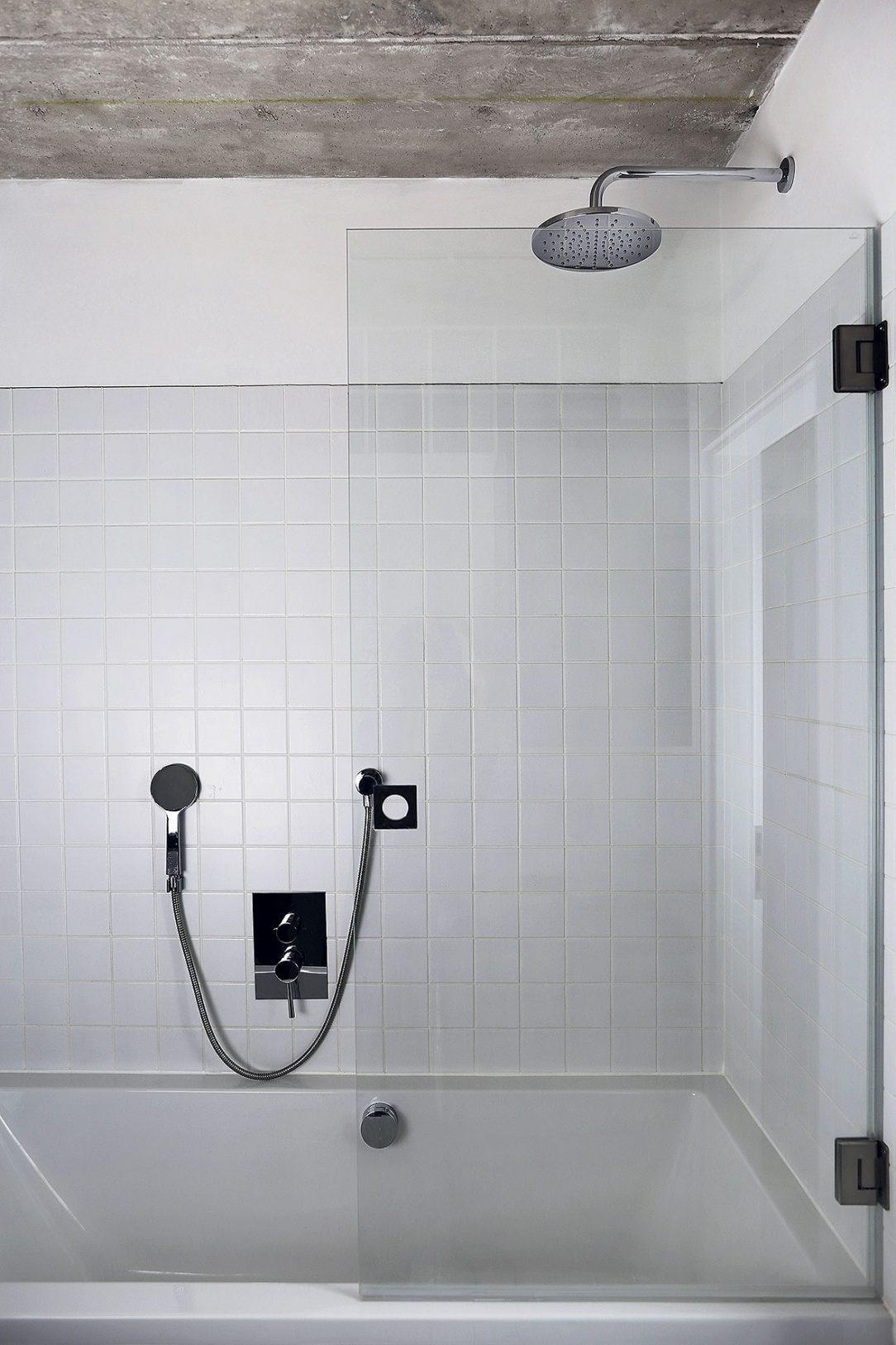 V koupelně je betonový strop kombinovaný s bílými obklady.