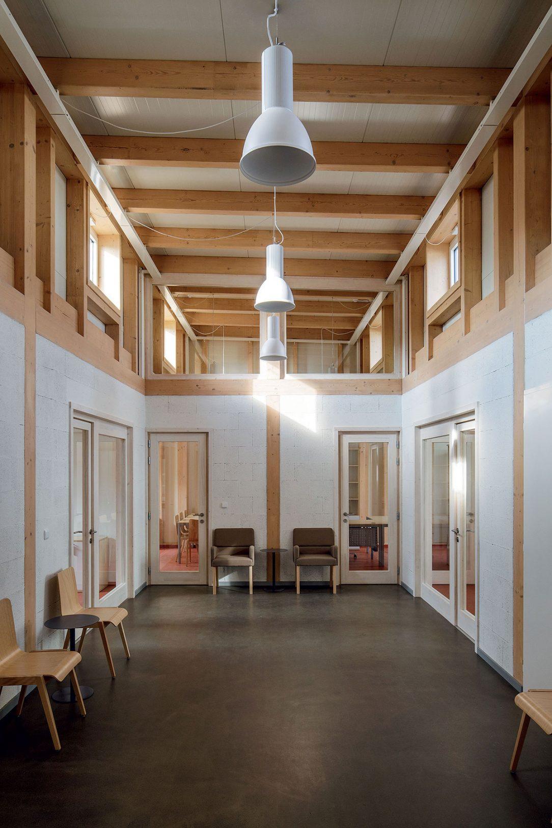 Jednoduchá architektura interiéru využívá dřevo bílou barvu a strukturu liaporových tvárnic.