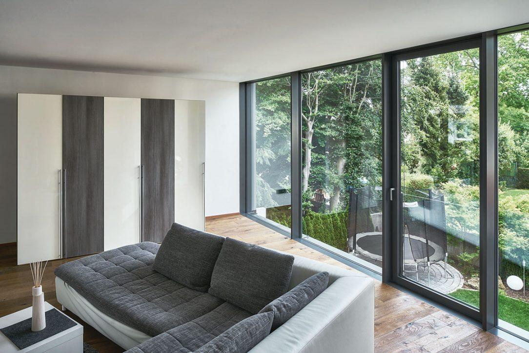 Obývací prostor v horním patře prosklené elementy na výšku místnosti z nichž jeden lze otevírat umožňují maximální přísun světla a výhled do zahrady