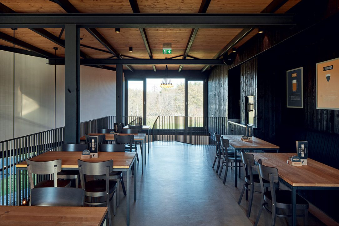 V interiéru restaurace se kombinuje černý kov a dřevěné obložení.