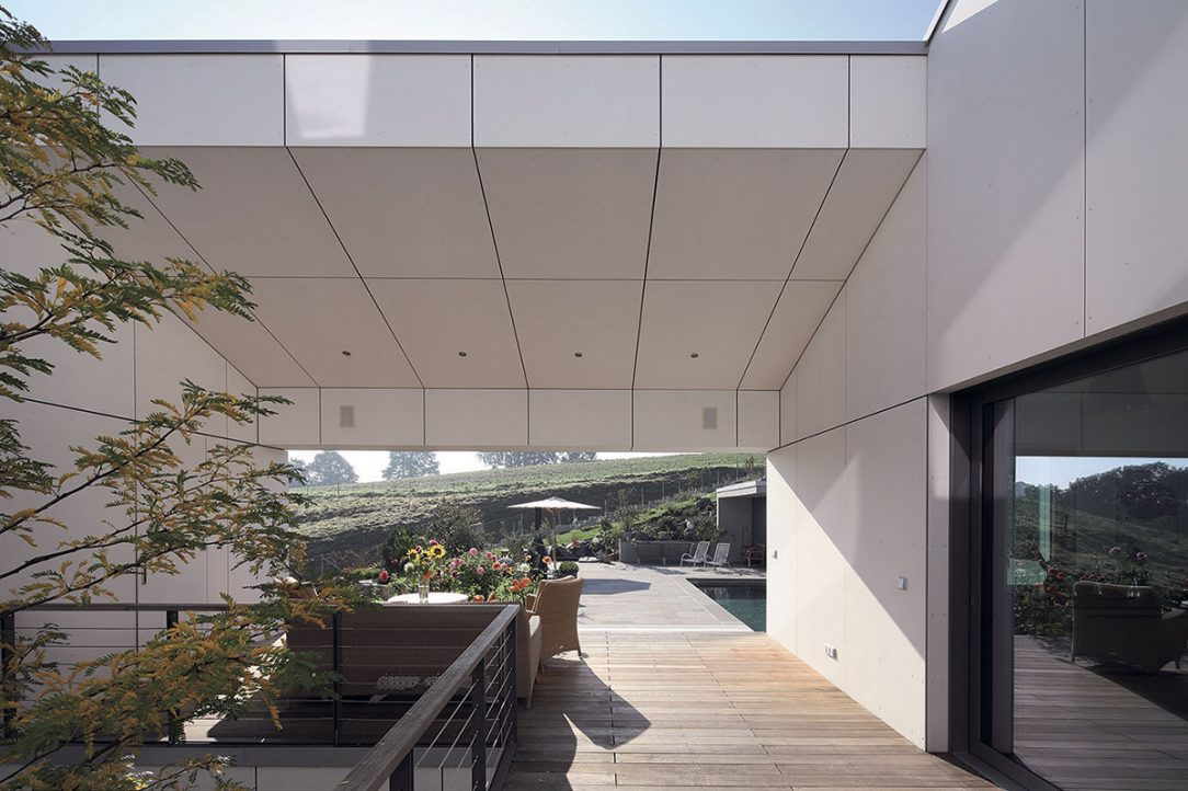 Fasádu nádvoří pasivního domu v Lauschka tvoří vláknocementové obklady. Pro maximální odraz denního světla jsou v čistě bílém barevném provedení.