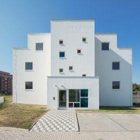 Východní průčelí domu je kvůli objemu schodiště a bytu v nejvyšším patře členitější.