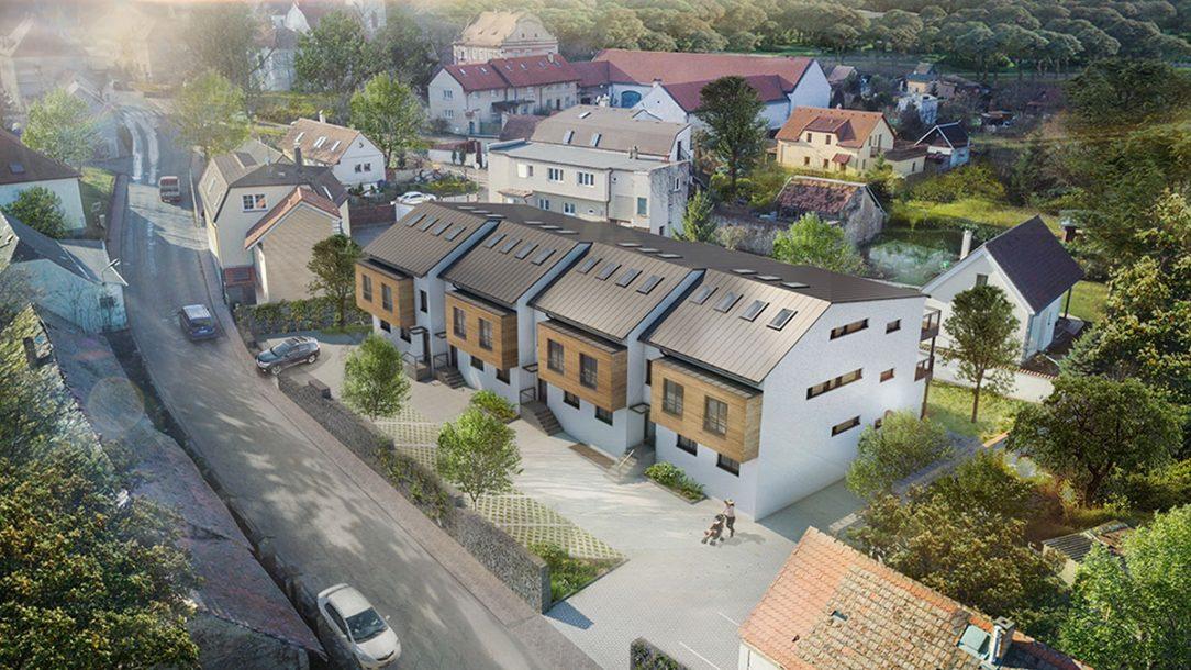 Rozdělení na čtyři řadové vily rozděluje celkový objem. Objekt tak lépe zapadá do okolního vesnického kontextu.