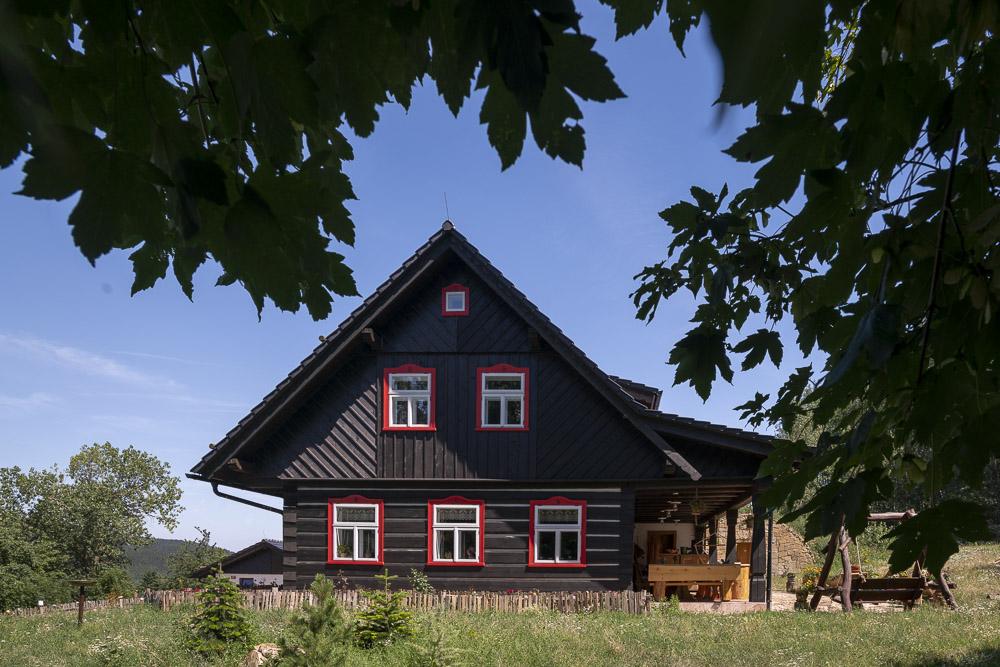 Příjemný vzhled dodávají stavbě bílé okenní rámy s červenými šambránami.