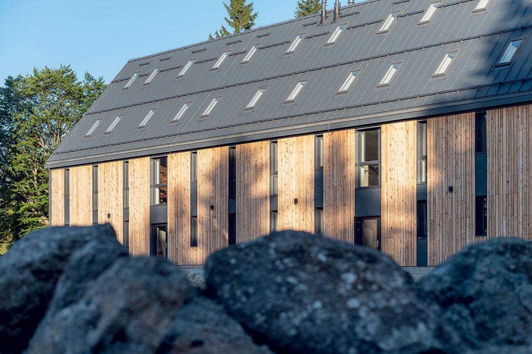 Antracitová střecha a okna ladí s okolní přírodou.