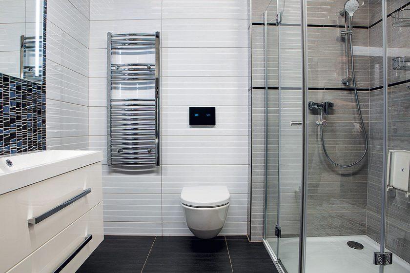 Elektronický dotykový splachovač toalety ve skleněném panelu.