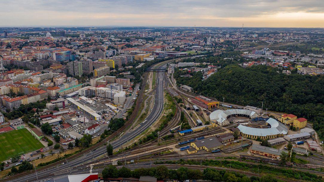 Pohled k Edenu. Původní trať Hostivař – Vršovice (vlevo), nové zaústění tratí Vršovice – Krč, odstavné nádraží jih a depo Praha (vpravo)