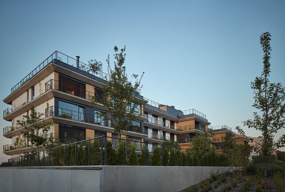 Zelená mozaika teras obíhající budovu