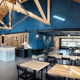 Tmavomodré štukové stěny ve spojení s bledým dřevem zajímavě dolaďují interiér restaurace.
