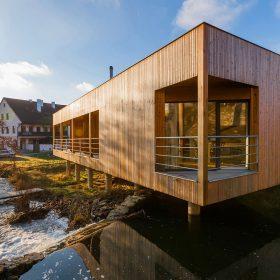 Dřevěný dům se zelenou střechou a vodopádem